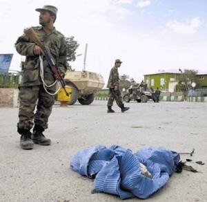 An Afghan soldier stands guard over a burqa used by a male Taliban suicide bomber to attack government buildings in Paktia Province.