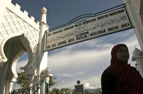 A woman walks past by a sign advising people to wear Muslim attire at Baiturrahman Grand Mosque in Banda Aceh. A local lawmaker says a controverisial bill allowing Shariah-style stoning and caning has gone into effect in the province. (Photo: Heri Juanda, AP)