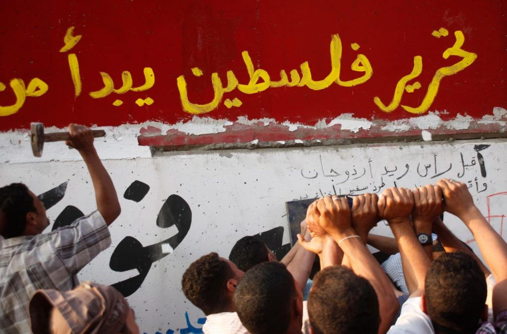 """Egyptian activists demolish a concrete wall built around a building housing the Israeli embassy in Cairo, Egypt, to protect it against demonstrators, Friday, Sept.9, 2011. Arabic reads """" liberation of Palestine begin from Egypt"""" (AP Photo/Amr Nabil)"""
