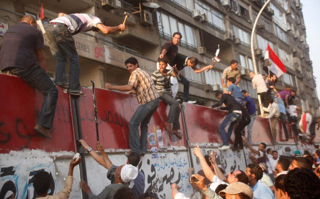 Some hundreds of Egyptian activists demolish a concrete wall built around a building housing the Israeli embassy in Cairo, Egypt, to protect it against demonstrators, as they raise their national Friday, Sept. 9, 2011. (AP Photo/Amr Nabil)