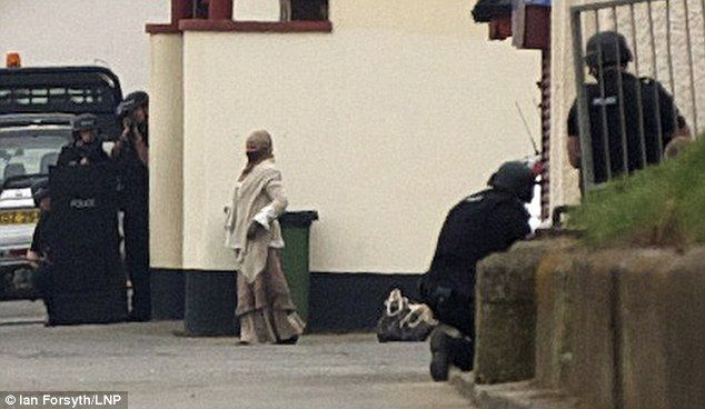 Armed Police surround the woman in Saltburn, Teesside, and take aim. Her bag is behind her.